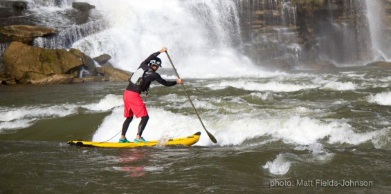 River SUP paddler on the waves.